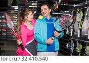 Купить «Girl and male in uniform choosing tennis rocket», фото № 32410540, снято 7 февраля 2018 г. (c) Яков Филимонов / Фотобанк Лори
