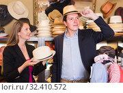 Купить «female and man choosing hats in the store», фото № 32410572, снято 2 мая 2017 г. (c) Яков Филимонов / Фотобанк Лори