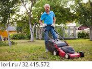 Купить «Positive elderly man with lawnmower when mowing the lawn», фото № 32415572, снято 30 мая 2020 г. (c) Яков Филимонов / Фотобанк Лори