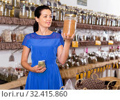 Купить «Woman choosing eco dried herbs sold by weight», фото № 32415860, снято 13 июня 2017 г. (c) Яков Филимонов / Фотобанк Лори