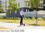 Купить «businessman with backpack riding electric scooter», фото № 32420540, снято 1 августа 2019 г. (c) Syda Productions / Фотобанк Лори