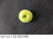 Купить «ripe green apple on slate stone background», фото № 32420640, снято 12 апреля 2018 г. (c) Syda Productions / Фотобанк Лори