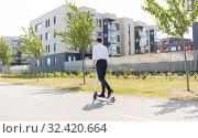 Купить «young businessman riding electric scooter outdoors», фото № 32420664, снято 1 августа 2019 г. (c) Syda Productions / Фотобанк Лори