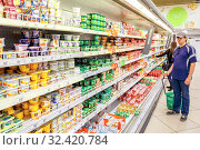 Russia, Samara, May 17, 2016: a young man with a basket stands in the department of dairy products in a large supermarket . Редакционное фото, фотограф Акиньшин Владимир / Фотобанк Лори