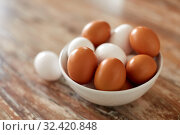 Купить «close up of eggs in ceramic bowl on wooden table», фото № 32420848, снято 16 августа 2018 г. (c) Syda Productions / Фотобанк Лори