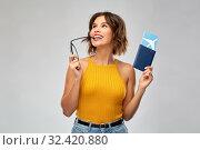 Купить «happy young woman with air ticket and passport», фото № 32420880, снято 30 сентября 2019 г. (c) Syda Productions / Фотобанк Лори