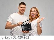 Купить «happy couple in white t-shirts with clapperboard», фото № 32420952, снято 6 октября 2019 г. (c) Syda Productions / Фотобанк Лори