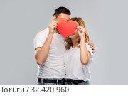 Купить «smiling couple hiding behind big red heart», фото № 32420960, снято 6 октября 2019 г. (c) Syda Productions / Фотобанк Лори