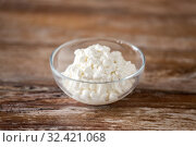 Купить «close up of cottage cheese in bowl on wooden table», фото № 32421068, снято 16 августа 2018 г. (c) Syda Productions / Фотобанк Лори