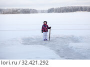 Купить «Young girl with crowbar in hand standing near cleared ice on lake for making ice-hole», фото № 32421292, снято 30 декабря 2014 г. (c) Кекяляйнен Андрей / Фотобанк Лори