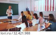 Купить «Female speaker giving lesson for university students in lecture hall», видеоролик № 32421988, снято 2 апреля 2020 г. (c) Яков Филимонов / Фотобанк Лори