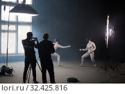 Купить «A fencing training in the studio - two women in protective costumes having a duel - two cameramans standing near the tripod and shooting the duel», фото № 32425816, снято 4 ноября 2019 г. (c) Константин Шишкин / Фотобанк Лори