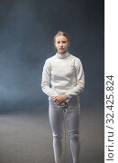 Купить «A young woman fencer standing with a sword down», фото № 32425824, снято 4 ноября 2019 г. (c) Константин Шишкин / Фотобанк Лори