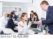 Купить «Upset girl sitting at laptop in office while dissatisfied businessman pointing», фото № 32426880, снято 21 апреля 2018 г. (c) Яков Филимонов / Фотобанк Лори