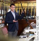 Man seller in hunting shop demonstrating shotgun. Стоковое фото, фотограф Яков Филимонов / Фотобанк Лори
