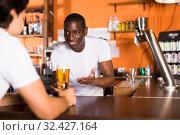 Купить «Young man bartender giving beer with foam to man client», фото № 32427164, снято 28 августа 2019 г. (c) Яков Филимонов / Фотобанк Лори