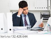 Купить «Adult male is reading documents about the transaction», фото № 32428644, снято 18 мая 2017 г. (c) Яков Филимонов / Фотобанк Лори