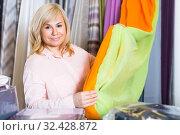 Купить «Mature woman customer choosing color curtains», фото № 32428872, снято 17 января 2018 г. (c) Яков Филимонов / Фотобанк Лори