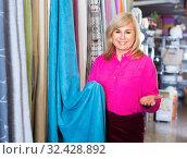 Купить «Positive mature woman seller showing curtain in the curtains shop», фото № 32428892, снято 17 января 2018 г. (c) Яков Филимонов / Фотобанк Лори