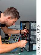 Купить «Ein Mann repariert einen Computer in einem Büro», фото № 32431316, снято 8 июля 2020 г. (c) age Fotostock / Фотобанк Лори