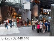 Group of European people has guided tour inside of Kyoto station concourse. Guide shows the upper level of building. Киото, Япония (2013 год). Редакционное фото, фотограф Кекяляйнен Андрей / Фотобанк Лори