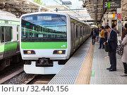 People wait the train on platform of railway station. It is the JR Yamanote Line most important train line in Tokyo city. Train bound for Shinagawa. Токио, Япония (2013 год). Редакционное фото, фотограф Кекяляйнен Андрей / Фотобанк Лори