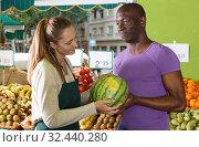 Купить «Smiling seller woman is helping man choose melone and watermelon», фото № 32440280, снято 26 мая 2018 г. (c) Яков Филимонов / Фотобанк Лори