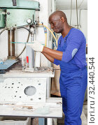 mature African American glazier working with glass on stationary drilling machine. Стоковое фото, фотограф Яков Филимонов / Фотобанк Лори