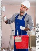 adult attentive man repairer working with roller in uniform, gloves and helmet. Стоковое фото, фотограф Яков Филимонов / Фотобанк Лори