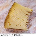 Купить «Slice of semi-hard cheese on a wooden table», фото № 32446824, снято 15 декабря 2019 г. (c) Яков Филимонов / Фотобанк Лори
