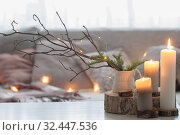 Купить «Composition of candles on white table against the background of sofa with plaids and pillows. Cozy home concept», фото № 32447536, снято 17 ноября 2019 г. (c) Майя Крученкова / Фотобанк Лори
