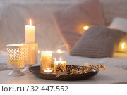 Купить «Christmas decoration with burning candles on white table against the background of sofa with plaids and pillows. Cozy home and holiday concept», фото № 32447552, снято 18 ноября 2019 г. (c) Майя Крученкова / Фотобанк Лори