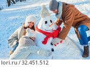 Glückliche Familie baut einen Schneemann zusammen im Garten im Winter. Стоковое фото, фотограф Zoonar.com/Robert Kneschke / age Fotostock / Фотобанк Лори