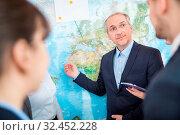 Manager erklärt an einer Weltkarte die internationale Planung und Business Strategie. Стоковое фото, фотограф Zoonar.com/Robert Kneschke / age Fotostock / Фотобанк Лори