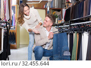 Купить «Cheerful loving couple deciding on new trousers», фото № 32455644, снято 9 декабря 2019 г. (c) Яков Филимонов / Фотобанк Лори