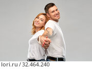 Купить «happy couple in white t-shirts holding hands», фото № 32464240, снято 6 октября 2019 г. (c) Syda Productions / Фотобанк Лори