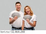 Купить «happy couple in white t-shirts with dollar money», фото № 32464288, снято 6 октября 2019 г. (c) Syda Productions / Фотобанк Лори