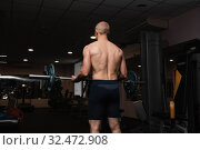 Купить «Muscular bodybuilder guy doing exercises with barbell in gym. Brutal strong athletic man pumping up muscles and train in gym workout.», фото № 32472908, снято 31 октября 2019 г. (c) Иван Карпов / Фотобанк Лори