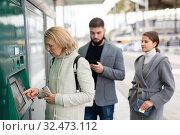 Купить «Passengers buying ticket at ticket vending machine», фото № 32473112, снято 16 декабря 2019 г. (c) Яков Филимонов / Фотобанк Лори