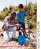 Купить «Man and boy with fish catch», фото № 32473240, снято 26 мая 2019 г. (c) Яков Филимонов / Фотобанк Лори