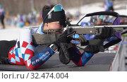 Sportswoman biathlete aiming, rifle shooting in prone position. Biathlete Shishkina Vlada Saint Petersburg in shooting range. Junior biathlon competitions East Cup (2019 год). Редакционное видео, видеограф А. А. Пирагис / Фотобанк Лори