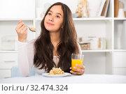 Купить «smiling girl eating cereals and drinking juice», фото № 32474324, снято 30 мая 2017 г. (c) Яков Филимонов / Фотобанк Лори