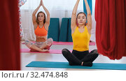 Купить «Yoga - two women sitting on the mats and doing breathing exercises - bright studio», видеоролик № 32474848, снято 9 декабря 2019 г. (c) Константин Шишкин / Фотобанк Лори