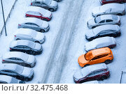 View from above at standing in lines snow covered cars in other sides of slippery road, winter parking lot near building. Стоковое фото, фотограф Кекяляйнен Андрей / Фотобанк Лори