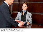 Gast an der Rezeption im Hotel bezahlt Rechnung mit Kreditkarte. Стоковое фото, фотограф Zoonar.com/Robert Kneschke / age Fotostock / Фотобанк Лори