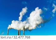 Die rauchenden Schlote einer Fabrik vor blauem Himmel. Aus Schornsteinen steigt weißer Rauch auf. Стоковое фото, фотограф Zoonar.com/Erwin Wodicka / age Fotostock / Фотобанк Лори