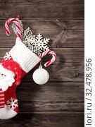 Купить «Christmas stocking with gifts hanging on dark old wooden background», фото № 32478956, снято 13 ноября 2019 г. (c) Майя Крученкова / Фотобанк Лори