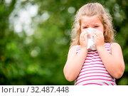 Mädchen mit Grippe beim Niesen in ein Taschentuch in der Natur. Стоковое фото, фотограф Zoonar.com/Robert Kneschke / age Fotostock / Фотобанк Лори