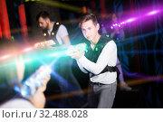 Купить «Excited guy laser tag player in bright beams», фото № 32488028, снято 25 апреля 2018 г. (c) Яков Филимонов / Фотобанк Лори