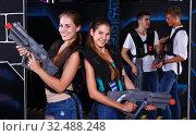 Купить «Two girls posing with laser guns», фото № 32488248, снято 27 августа 2018 г. (c) Яков Филимонов / Фотобанк Лори